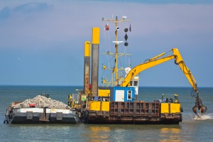 Industrial Barge with an Excavator working to build a breakwater, Baltic Sea, Germany